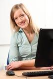 Schöne glückliche blonde Frau am Bürocomputer Stockfotos