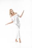 Schöne glückliche blonde Frau in der weißen Bluse und in den Hosen auf weißem Hintergrund Stockfotografie