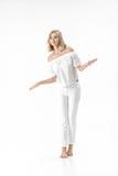 Schöne glückliche blonde Frau in der weißen Bluse und in den Hosen auf weißem Hintergrund Stockfoto