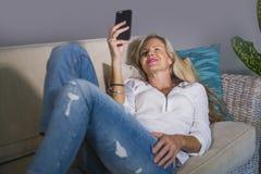 Schöne glückliche blonde Frau frühes 40s entspannte sich zu Hause Wohnzimmer unter Verwendung des Internet-Social Media auf Handy Stockbild