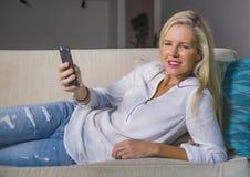 Schöne glückliche blonde Frau frühes 40s entspannte sich zu Hause Wohnzimmer unter Verwendung des Internet-Social Media auf Handy Stockbilder