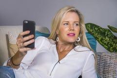 Schöne glückliche blonde Frau frühes 40s entspannte sich zu Hause Wohnzimmer unter Verwendung des Internet-Social Media auf Handy Lizenzfreies Stockfoto