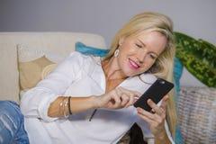 Schöne glückliche blonde Frau frühes 40s entspannte sich zu Hause Wohnzimmer unter Verwendung des Internet-Social Media auf Handy Lizenzfreies Stockbild