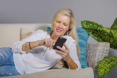Schöne glückliche blonde Frau frühes 40s entspannte sich zu Hause Wohnzimmer unter Verwendung des Internet-Social Media auf Handy Stockfoto