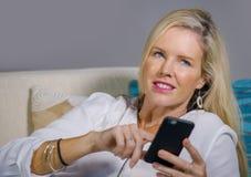 Schöne glückliche blonde Frau frühes 40s entspannte sich zu Hause Wohnzimmer unter Verwendung des Internet-Social Media auf Handy Lizenzfreie Stockfotos
