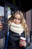 Schöne glückliche blonde junge kaukasische Frau, die draußen ein selfie auf Smartphone im Park im Herbst nimmt Stockbild