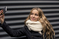 Schöne glückliche blonde junge kaukasische Frau, die draußen ein selfie auf Smartphone im Park im Herbst nimmt Stockfotografie