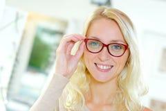 Schöne glückliche blonde weibliche schauende Kamera Stockfotografie