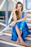 Schöne glückliche Blondine, die draußen in einem blauen Kleid lächeln Stockbild