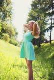 Schöne glückliche Blondine im Kleid draußen Stockbilder