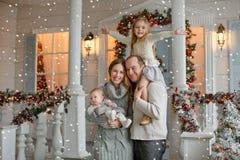 Schöne glückliche Familie mit kleinem Mädchen in gestrickten Strickjacken sind lizenzfreie stockfotos