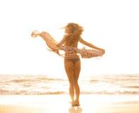 Schöne glückliche Frau auf Strand bei Sonnenuntergang Stockfoto