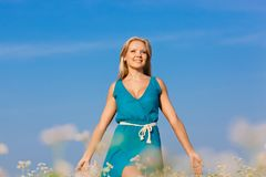 Schöne glückliche Frau, die auf Blumenfeld geht Lizenzfreies Stockbild