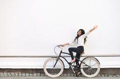 Schöne glückliche Frau, die auf Fahrrad sitzt und Gruß gestu gibt Lizenzfreies Stockfoto