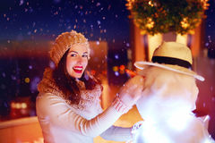 Schöne glückliche Frau, die Schneemann unter magischem Winterschnee macht lizenzfreies stockfoto