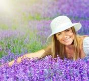 Schöne glückliche Frau, die sich auf Lavendelfeld hinlegt Lizenzfreie Stockfotos