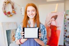 Schöne glückliche Frau, die Tablette des leeren Bildschirms in der Kunstwerkstatt hält Lizenzfreies Stockbild