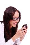 Schöne glückliche Frau, die Text am Handy sendet Stockbilder