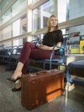 Schöne glückliche Frau im Flughafenwarteraum Frauen mit eisigem Margarita Stockbild
