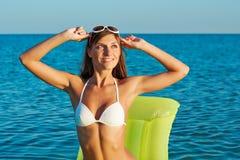 Schöne glückliche Frau im weißen Bikini mit gelber aufblasbarer Matratze auf dem Strand Lizenzfreies Stockfoto