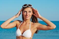 Schöne glückliche Frau im weißen Bikini mit gelber aufblasbarer Matratze auf dem Strand Stockbild