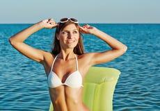 Schöne glückliche Frau im weißen Bikini mit gelber aufblasbarer Matratze auf dem Strand Stockfotografie