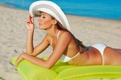 Schöne glückliche Frau im weißen Bikini mit gelber aufblasbarer Matratze auf dem Strand Lizenzfreie Stockfotos