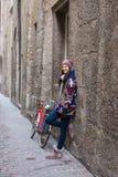 Schöne glückliche Frau ist, die nahe bei einem Fahrrad in einem kleinen a stehen Lizenzfreie Stockfotos