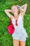 Schöne glückliche Frau liegt auf dem Gras im Sommer stockfotografie