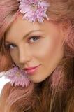 Schöne glückliche Frau mit dem rosa Haar und den Blumen Stockfoto