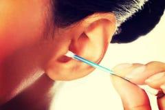 Schöne, glückliche Frau säubert ihr Ohr stockbild