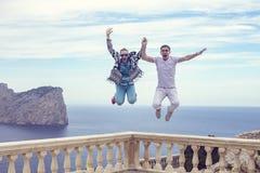 Schöne glückliche Freunde oder ein Paar, das Spaß hat und das Leben beim Springen genießt Stockbild