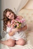Schöne glückliche junge Blondine mit einem Blumenstrauß von Blumen im Schlafzimmer Stockfotos