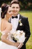 Schöne glückliche junge Braut, die hübschen Bräutigam in der sonnenbeschienen Gleichheit küsst Stockbilder
