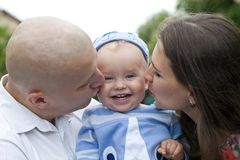 Schöne glückliche junge Familie mit Baby stockfotografie