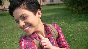 Schöne glückliche junge Frau, die das selfie und Lachen, stehend auf Gras im Park nahe Hochschulhintergrund nimmt stock video footage