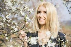 Schöne glückliche junge Frau, die Geruch in einem blühenden Frühling genießt stockfoto