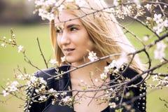 Schöne glückliche junge Frau, die Geruch in einem blühenden Frühlingsgarten genießt stockfoto