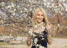 Schöne glückliche junge Frau, die Geruch in einem blühenden Frühlingsgarten genießt stockbilder