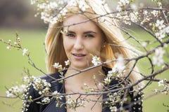 Schöne glückliche junge Frau, die Geruch in einem blühenden Frühlingsgarten genießt lizenzfreies stockfoto