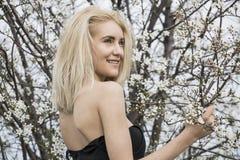 Schöne glückliche junge Frau, die Geruch in einem blühenden Frühlingsgarten genießt stockfotografie