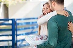 Schöne glückliche junge Frau, die ihren Freund oder Ehemann, nachdem eine Geschenkbox umarmt empfangen worden ist stockfoto