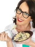 Schöne glückliche junge hispanische Frau, die eine Platte des vegetarischen Linguine mit Spinat und Pilzen isst Stockfoto