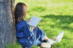Schöne, glückliche junge Studentin, die ein Buch sitzt auf grünem Gras unter einem Baum nahe Campus, Universität, Schule, Ausbild stockfotos