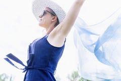 Schöne glückliche kaukasische Frau, die einen Schal über dem bewölkten Himmel wellenartig bewegt lizenzfreie stockfotografie