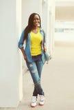 Schöne glückliche lächelnde afrikanische Frau, die ein Jeanshemd trägt stockbild