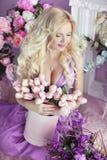 Schöne glückliche lächelnde blonde Frau mit langer gewellter Frisur herein Stockfoto
