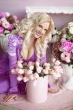 Schöne glückliche lächelnde blonde Frau mit langer gewellter Frisur herein Lizenzfreie Stockfotografie