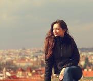 Schöne glückliche lächelnde Frau, die auf Prag-Stadtpanorama schaut stockfotografie