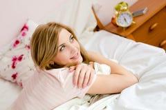 Schöne glückliche lächelnde junge blonde Frau im Bett Lizenzfreies Stockbild